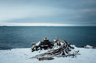 Derek Akeya sits in a hunting blind on the coast of St. Lawrence Island, scanning for walrus or seal. 11/22/16.