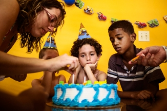 Sebastián Alvarado, 8, waiting as his mother, Magdanamay Colón, prepared the candles for his birthday cake in Aibonito, a town in the mountainous area of the island. Aug. 5, 2012.